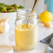 glass mason jar filled with Homemade Caesar Dressing, with a spoon inside of the jar