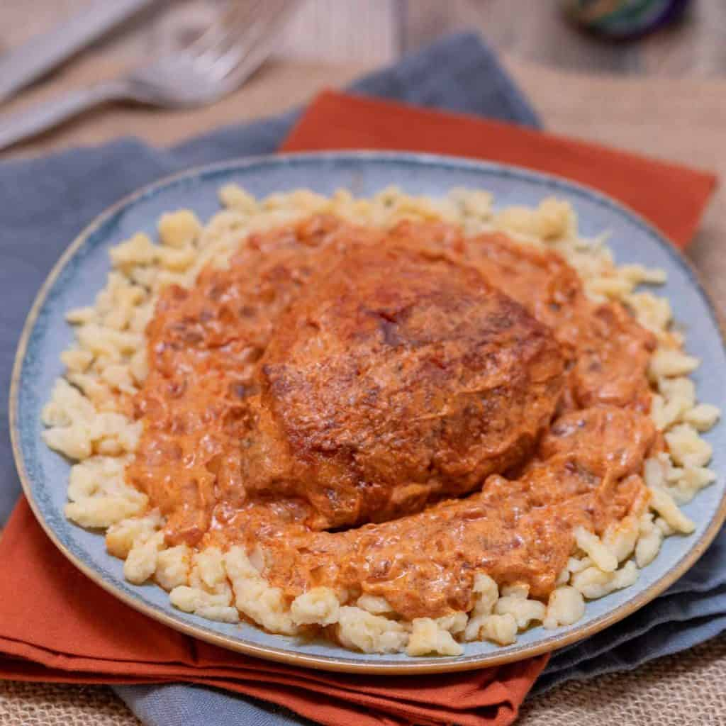 Close up of blue plate holding a portion of Chicken Paprikash
