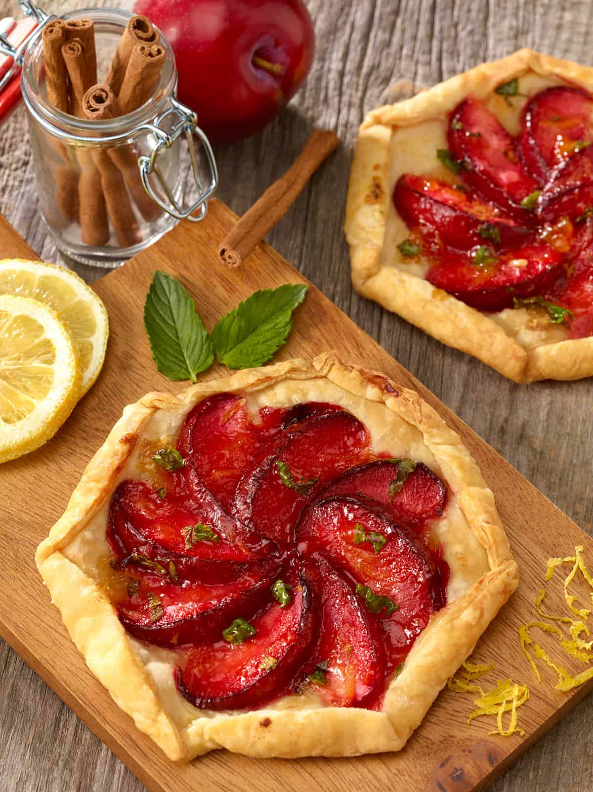 Wooden board holding an Individual Plum Tart, with a second tart to the side