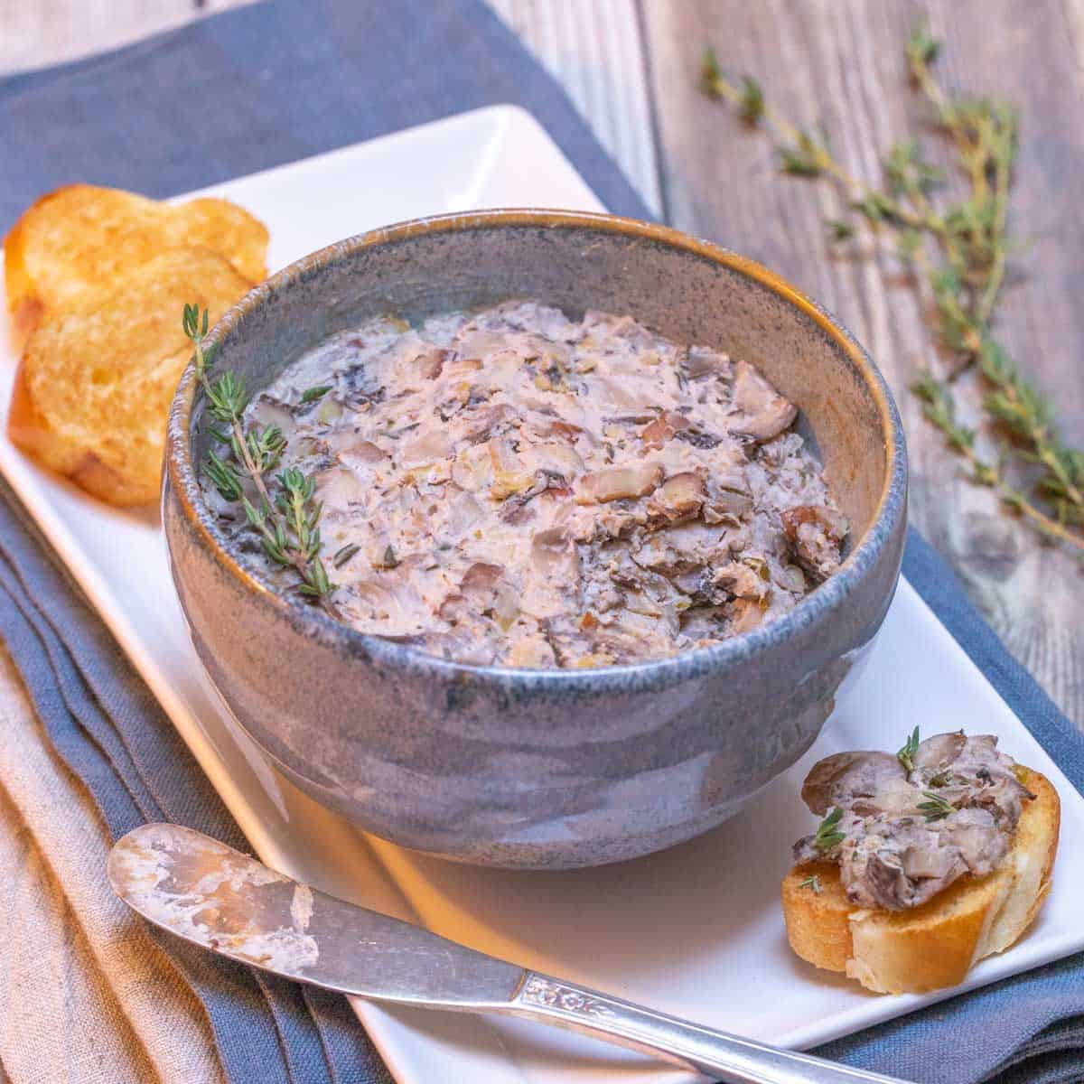 Blue bowl filled with Mushroom Pâté, with toasted baguette slices on the side