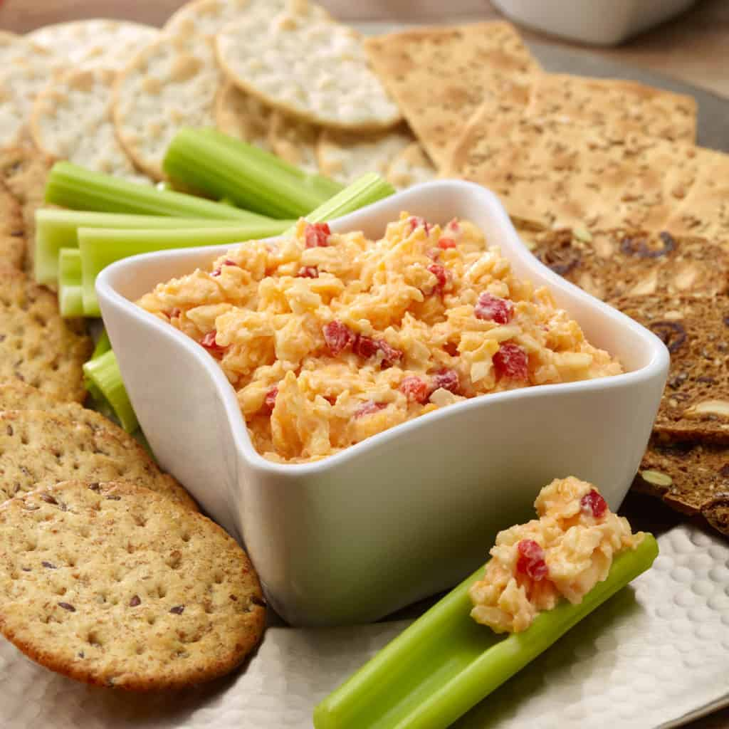 Pimiento Cheese Spread in a white bowl with celery sticks and crackers