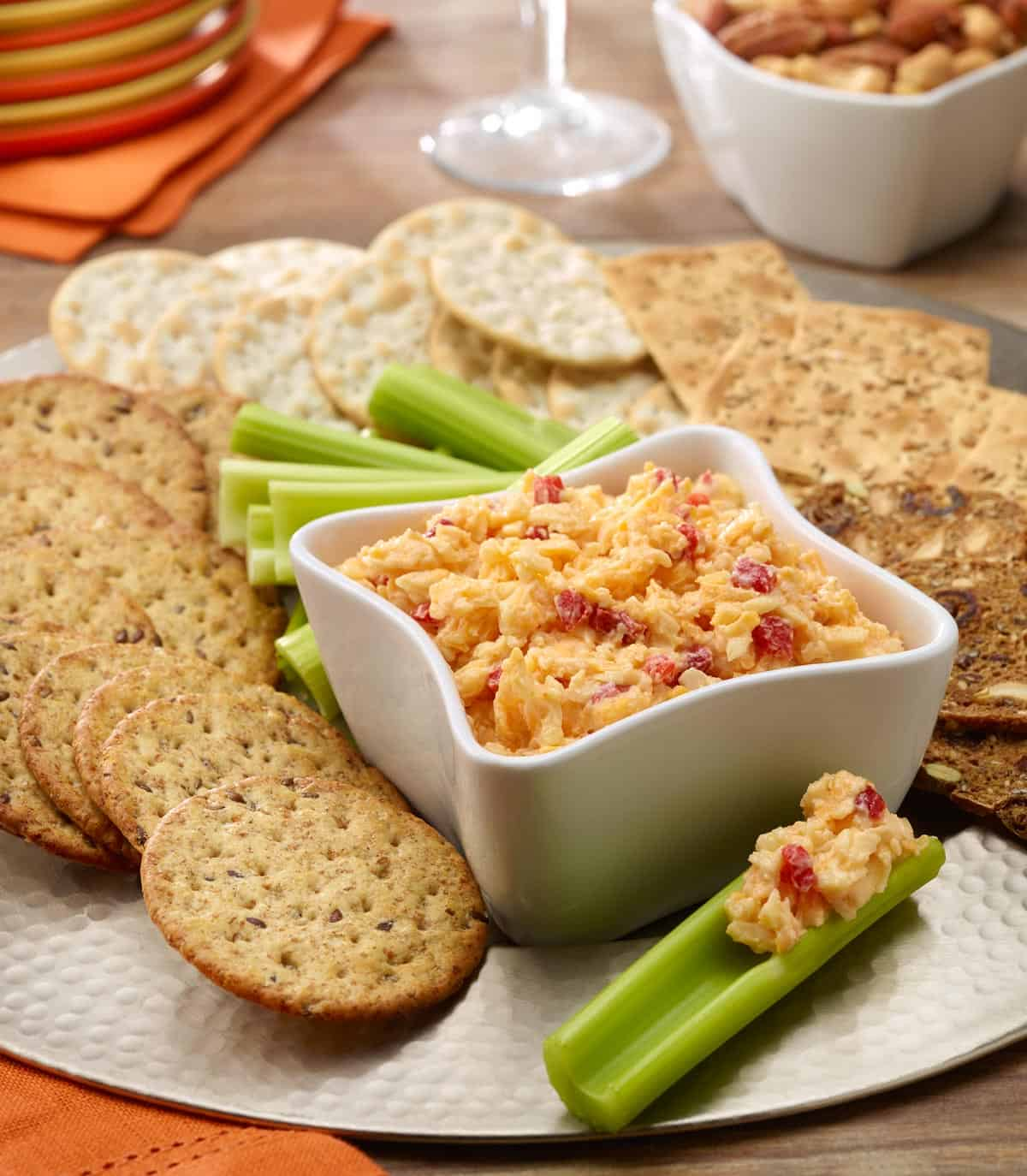 Pimiento cheese spread in a white bowl wih celery sticks and crackers