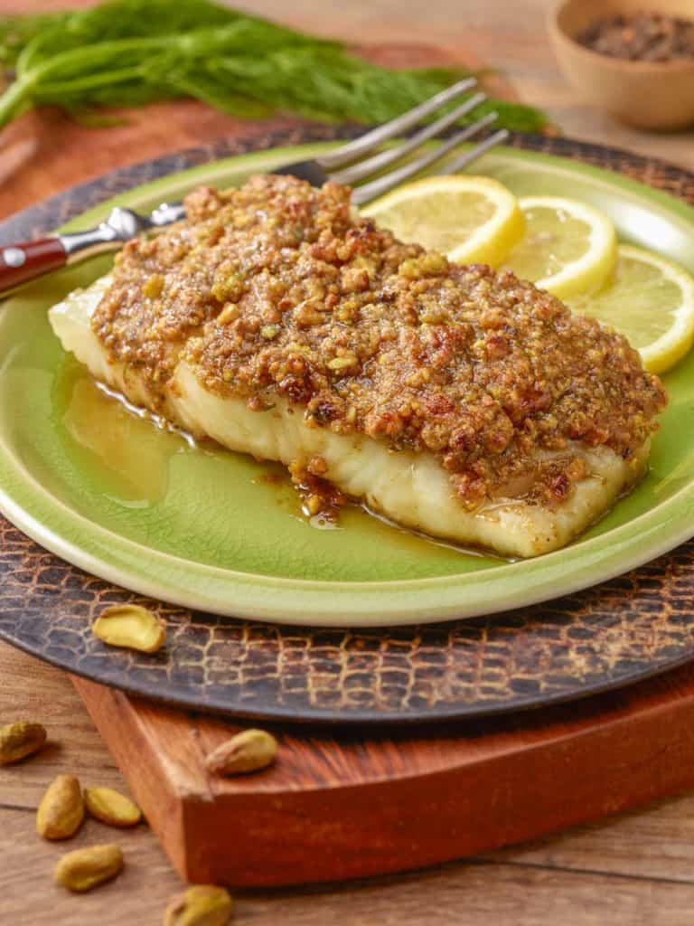 A single serving of Pistachio Crusted Fish, sitting on a light green plate that's on a cutting board.