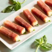 Narrow rectangular white platter filled with Prosciutto-Wrapped Smoked Mozzarella Sticks