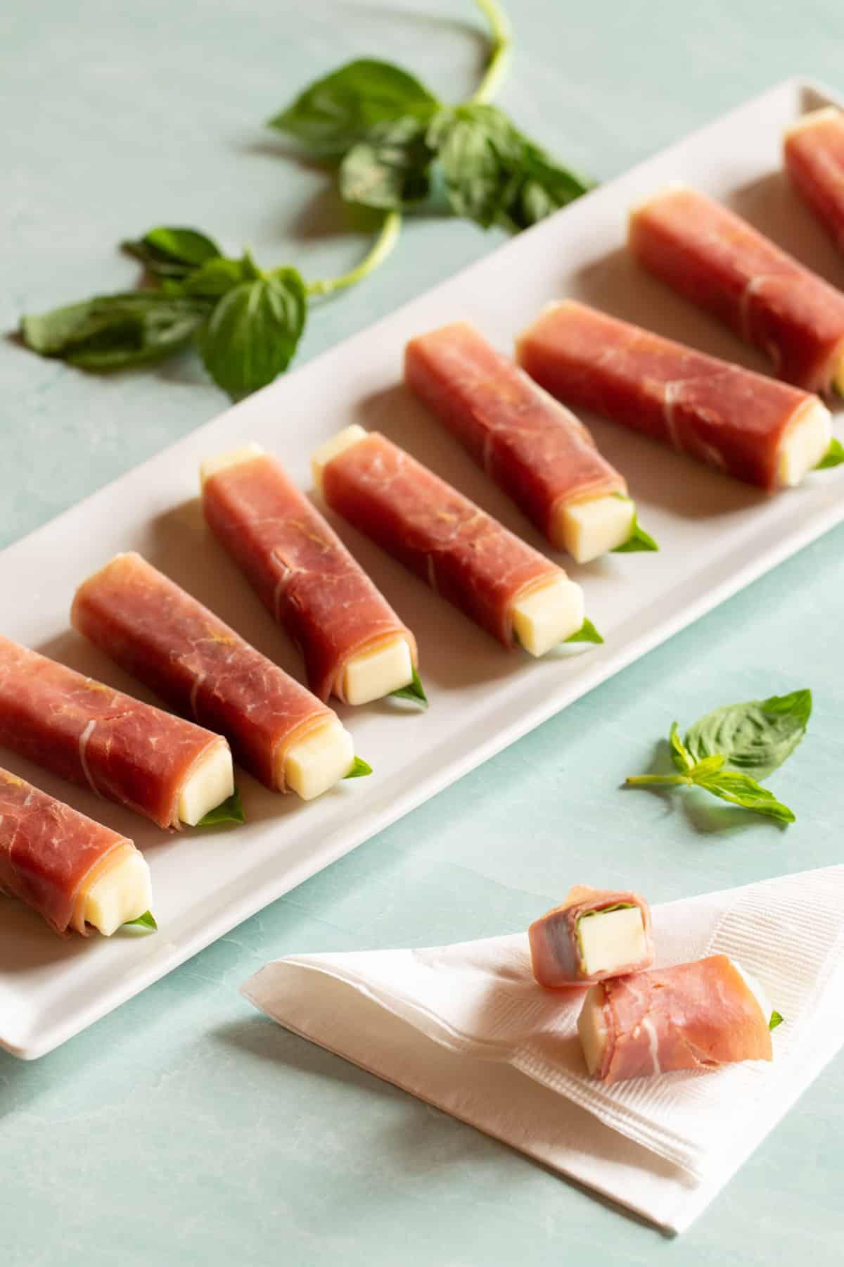 White rectangular platter filled with Prosciutto-Wrapped Smoked Mozzarella Sticks