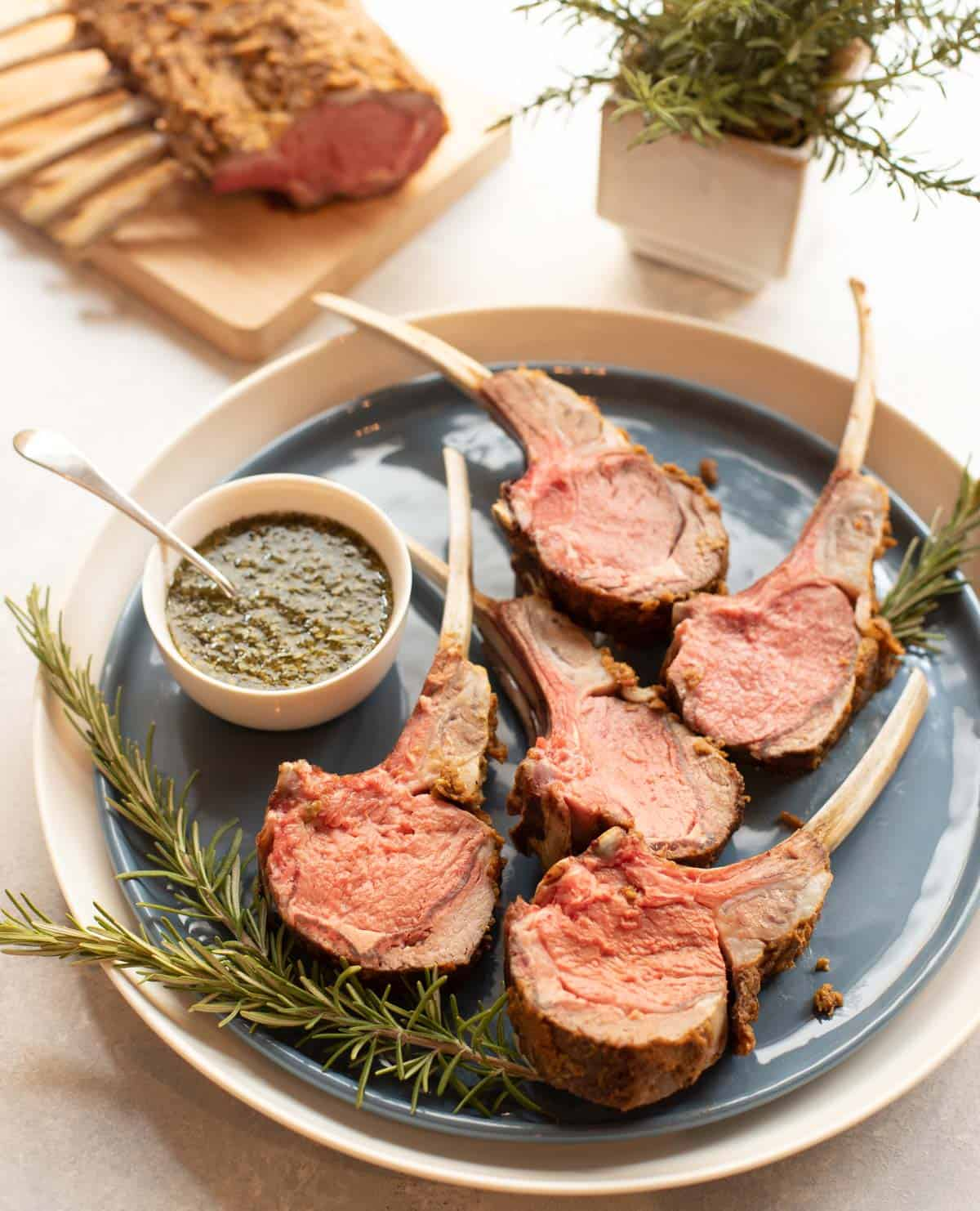 Blue plate with Mustard Crusted Rack of Lamb, sliced, with Fresh Mint Sauce on the side