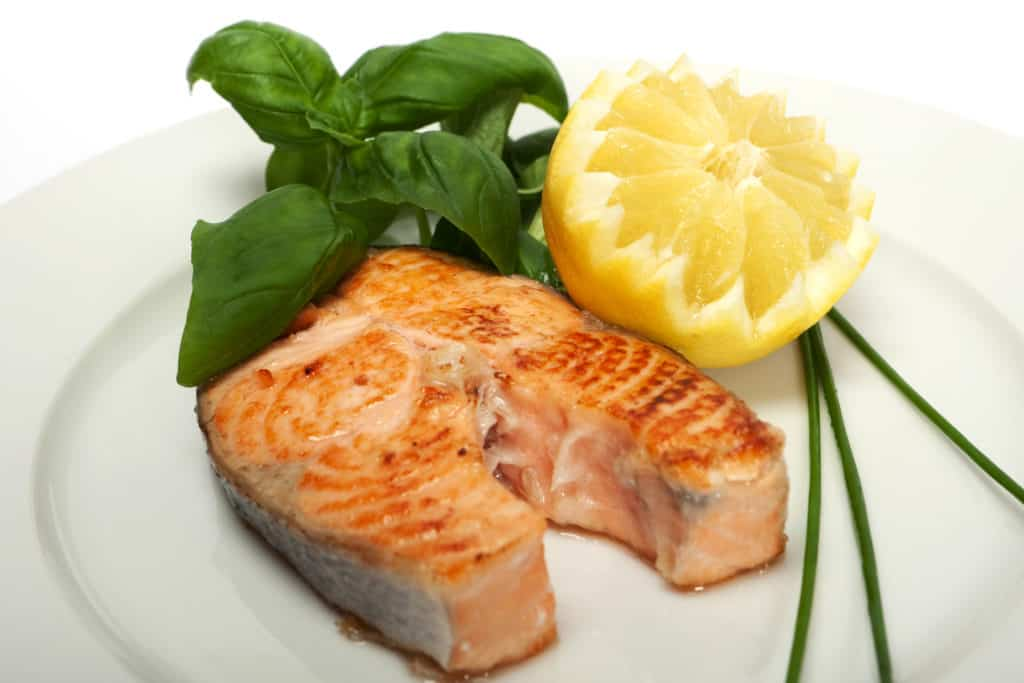 Single serving of Roasted Salmon Steaks on a white place with half lemon and basil leaves on the side