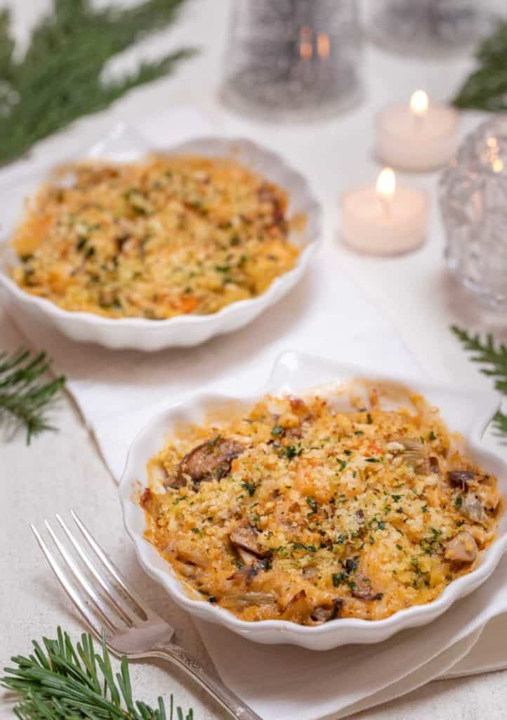 Two individual shelll dishes filled with seafood au gratin