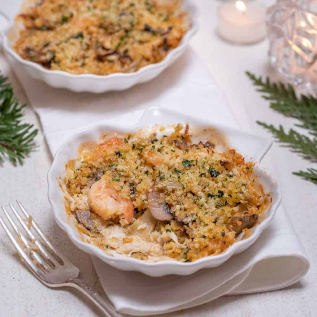 Shell shaped dish filled with an individual serving of Shrimp and Crab Au Gratin