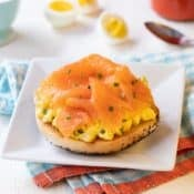 Square white plate with Toasted Bagel with Egg Salad and Smoked Salmon