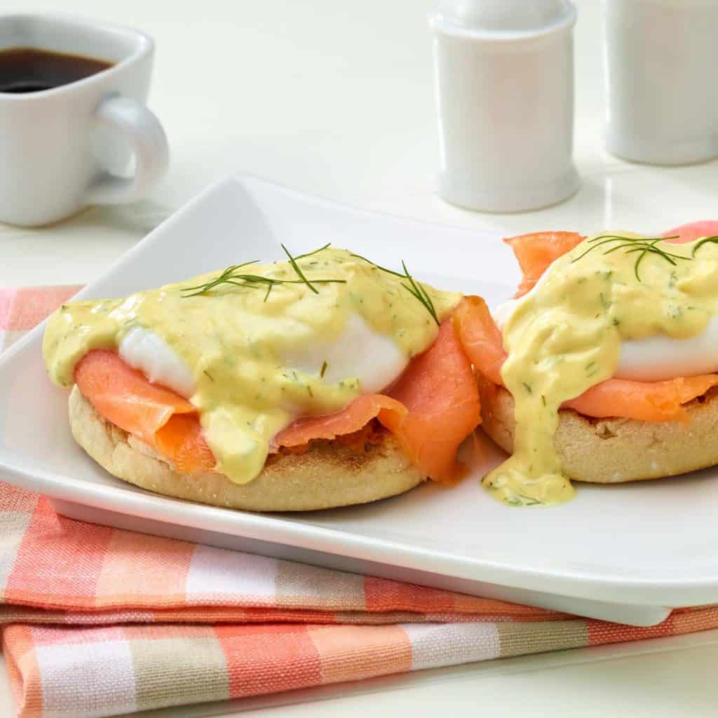 Colorful shot of delicious Smoked Salmon Eggs Benedict with Mustard Dill Sauce