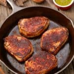 cast iron skillet with Spicy Pork Chops with Chimichurri Sauce on the side