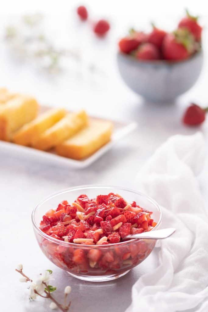 Clear bowl showing Strawberry Topping with slices of lemon bread in the background