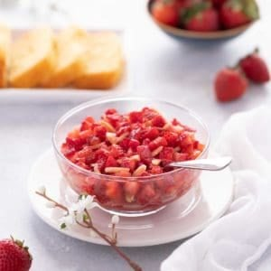 Close up of glass bowl showing Strawberry Topping, with sliced cake in the background