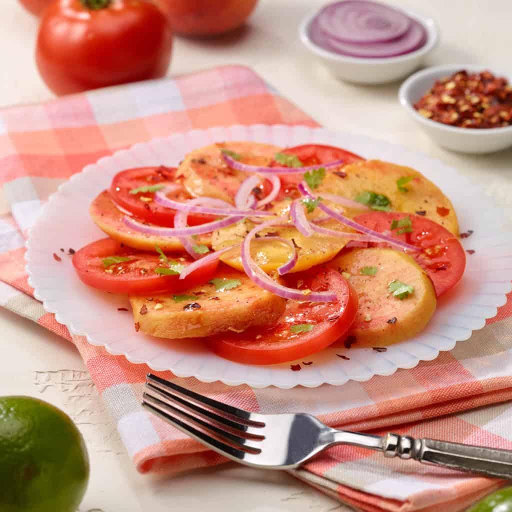 Sliced tomato peach salad on a white plate