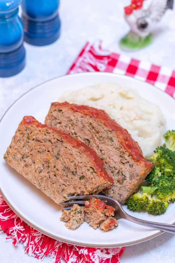 white plate holding two slices of Easy Turkey Meatloaf, mashed potatos and broccoli