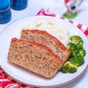 close up of white plate showing two slices of Easy Turkey Meatloaf, with mashed potatos and broccoli