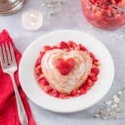 A round white plate holds a single serving of Valentine's Mini Cakes with Strawberry Almond Salsa