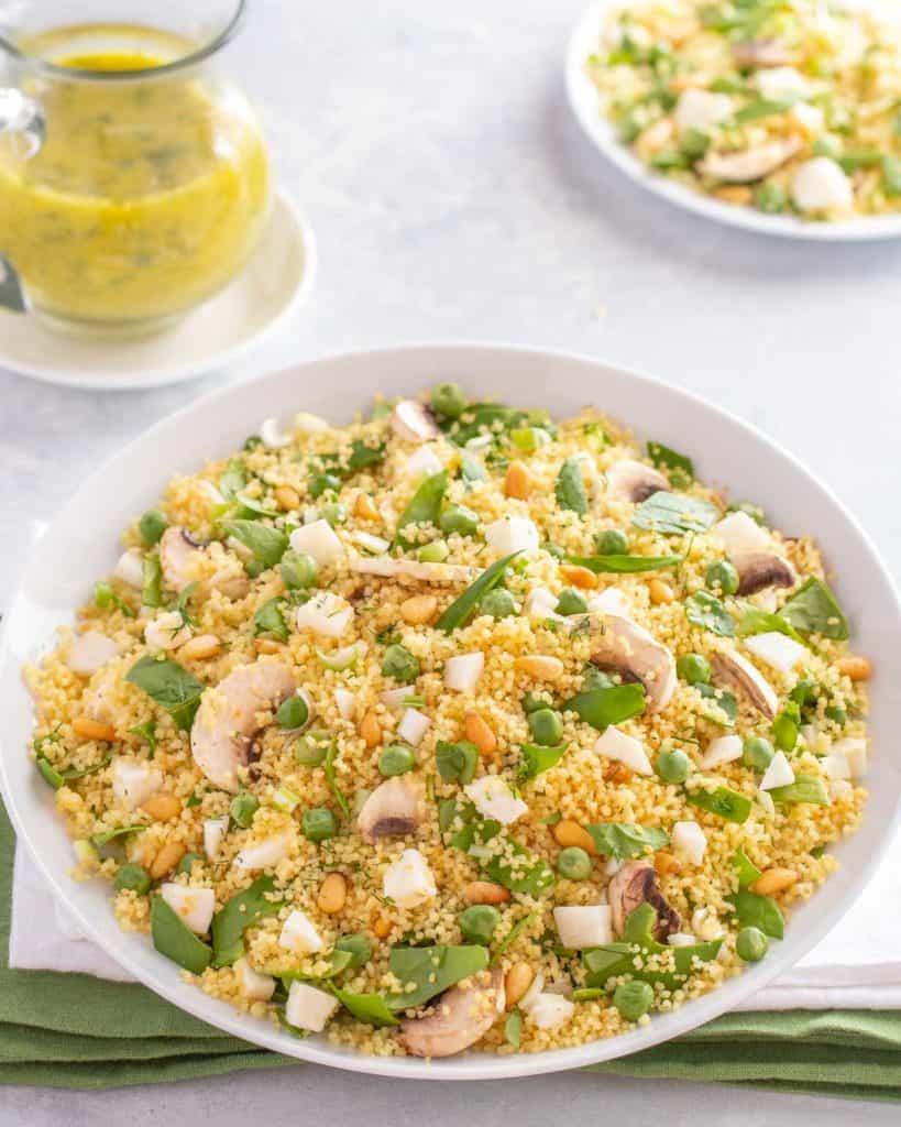 White bowl holding Vegetable Couscous: carafe of Dill Vinaigrette alongside