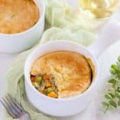 Small white dish holding one serving of Vegetarian Pot Pie with part of the crust removed to show filling