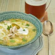White Bean and Chicken Chili in a blue bowl with a mug of beer